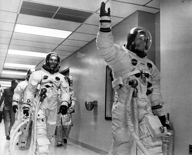 Posadka Apolla 11 na poti proti vesoljskemu plovilu, ki jih bo odpeljalo na Luno. Prvi Neil Armstrong, sledita mu Edwin 'Buzz' Aldrin in Michael Collins.